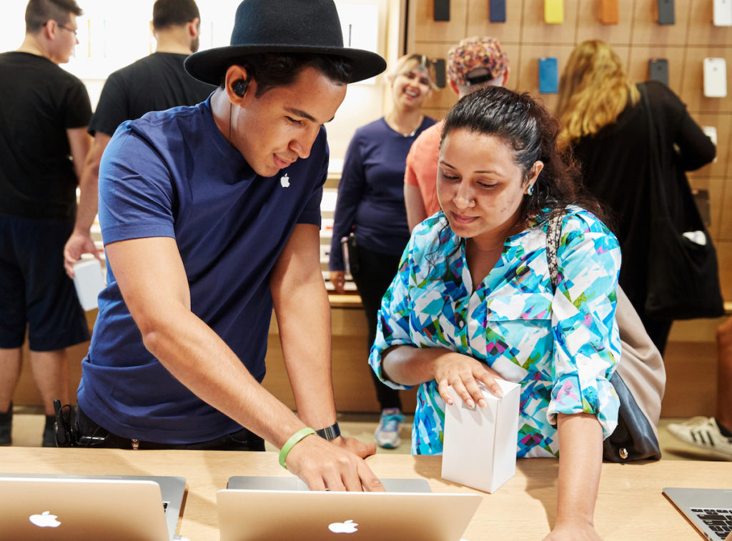 A store employee points to a Mac